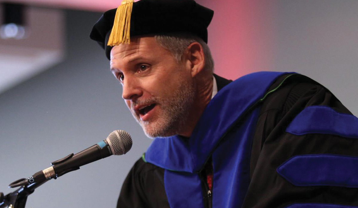 Bruce Pinkleton wearing commencement attire and speaking during a ceremony