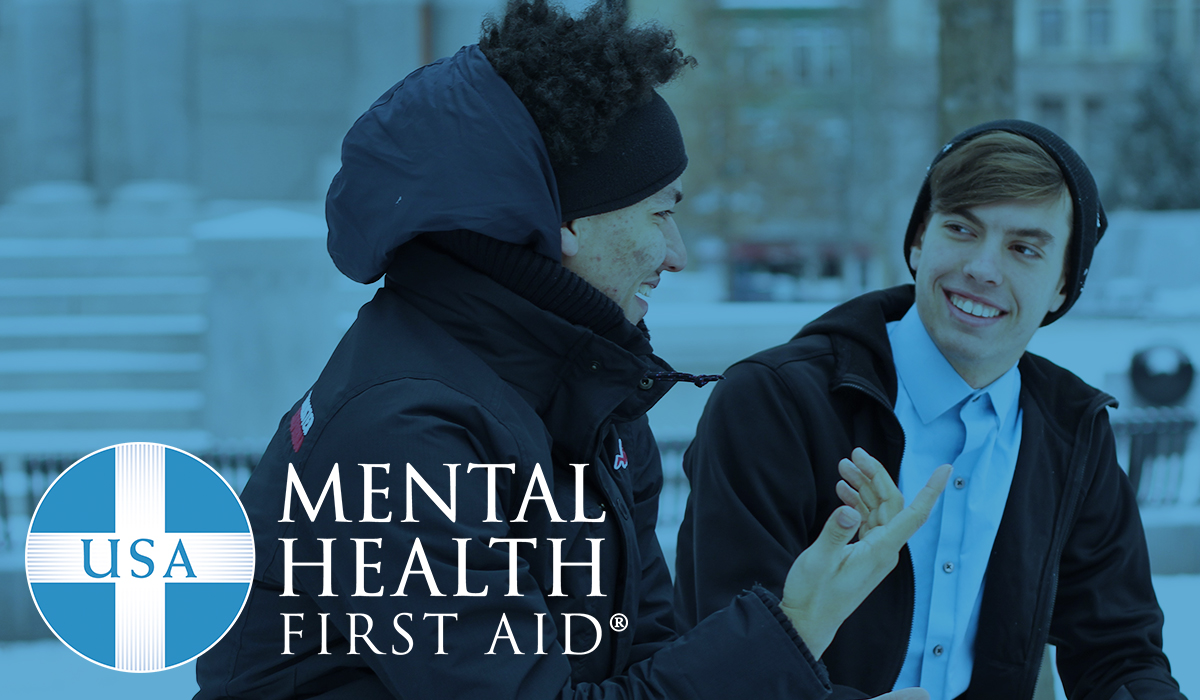 Mental Health First Aid logo and two students talking to one another.